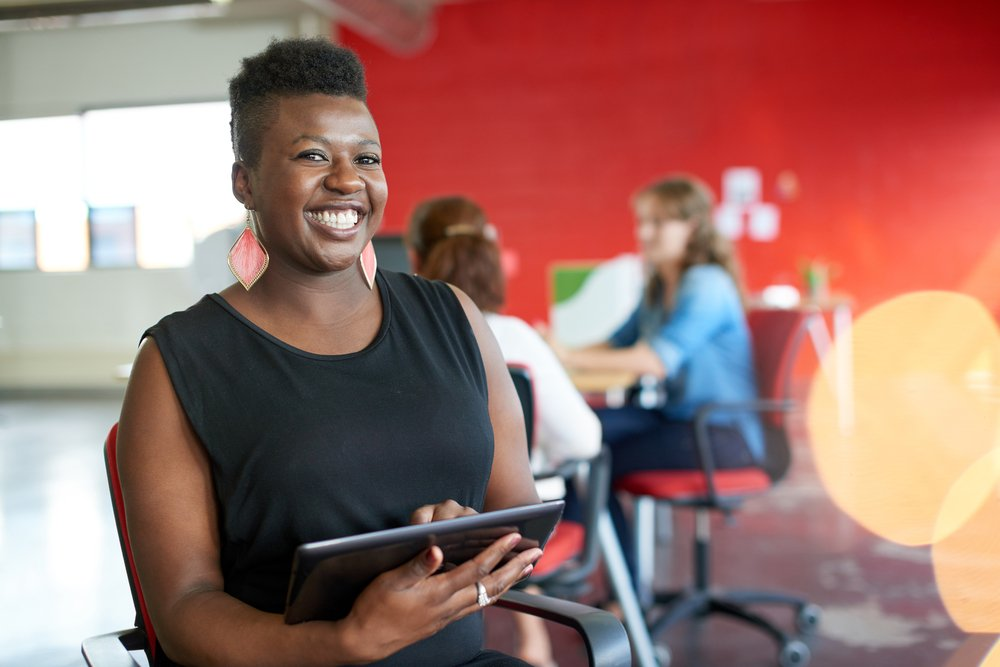 Confident female designer working on a digital tablet in red creative office space-2