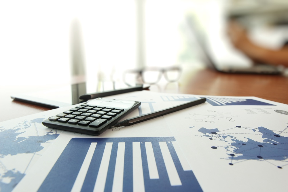 business documents on office table with calculator and digital tablet and man working in the background